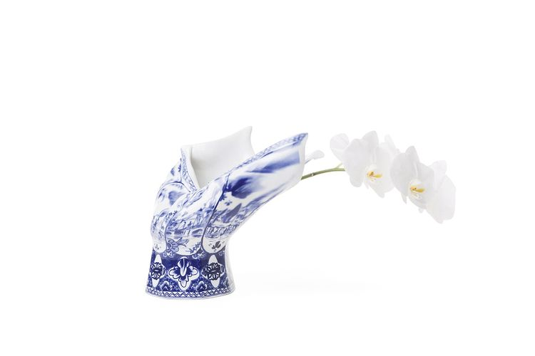 "<i>Blow Away Vase</i> by Front.  ""This classic Royal Blue Delft porcelain vase has experienced something truly bizarre: it has been blown aside by a powerful gush of wind. The wind motion has become part of its features and the beauty of the vase lies in"