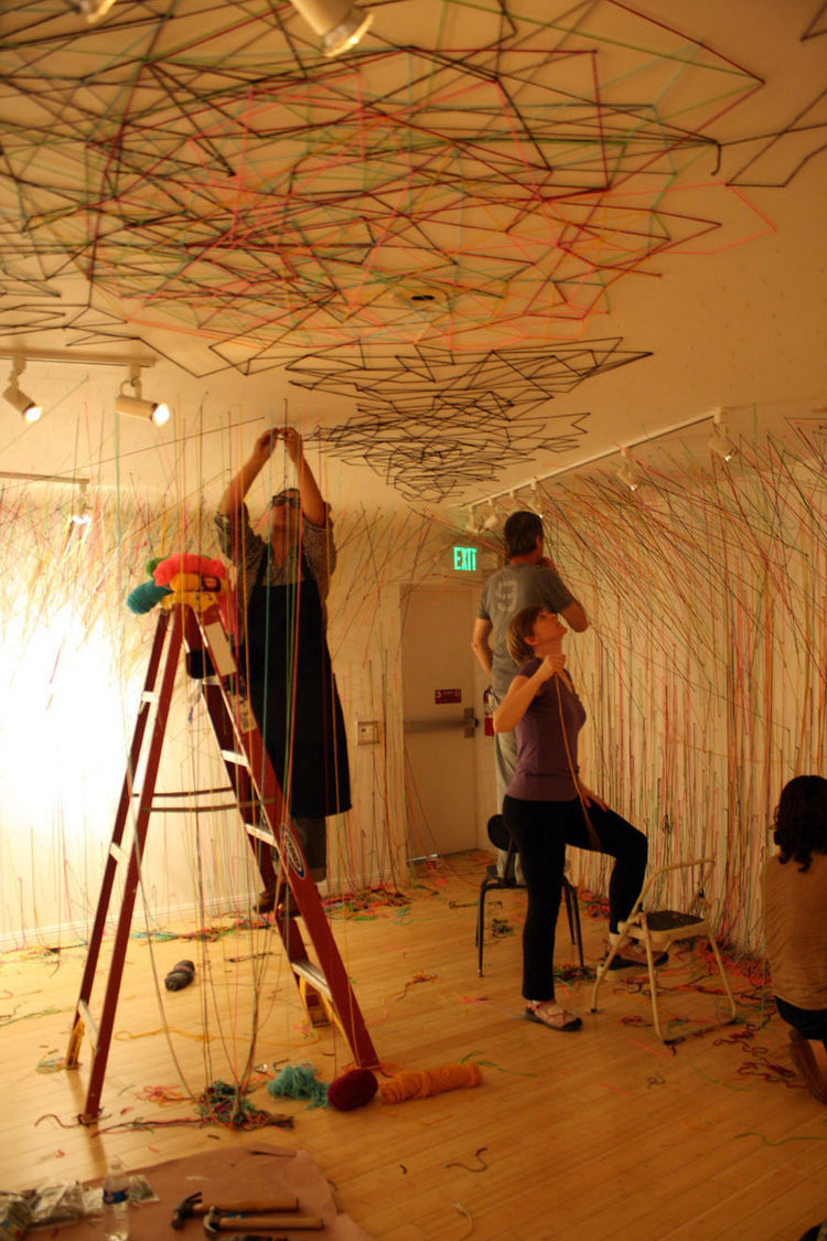 """Aguiñiga's installation was truly a handmade process, """"When you are having to stand on a ladder and weave way above your head, your arms are pretty tired afterward."""" From ceiling to wall to floor and back again, yards and yards of string were crisscrossed"""