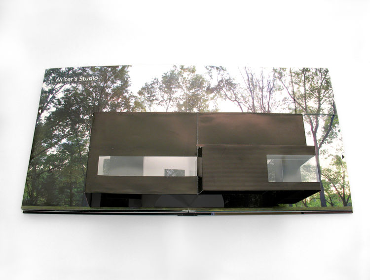Here's the boxy Writer's Studio in Ghent, New York, with open glass corners that offer an unimpeded view of the surrounding forest. Up in the right-hand corner of the page is a camouflaged mini-book, with photos illustrating the interior space.