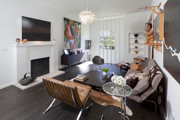 "The living room, reached by the main staircase off the entrance. The Mies chair is the first piece of modern furniture Popp purchased, on layaway. ""It took me two years to pay it off,"" he says. Around the coffee table from B&B Italia are an Eames rocker a"