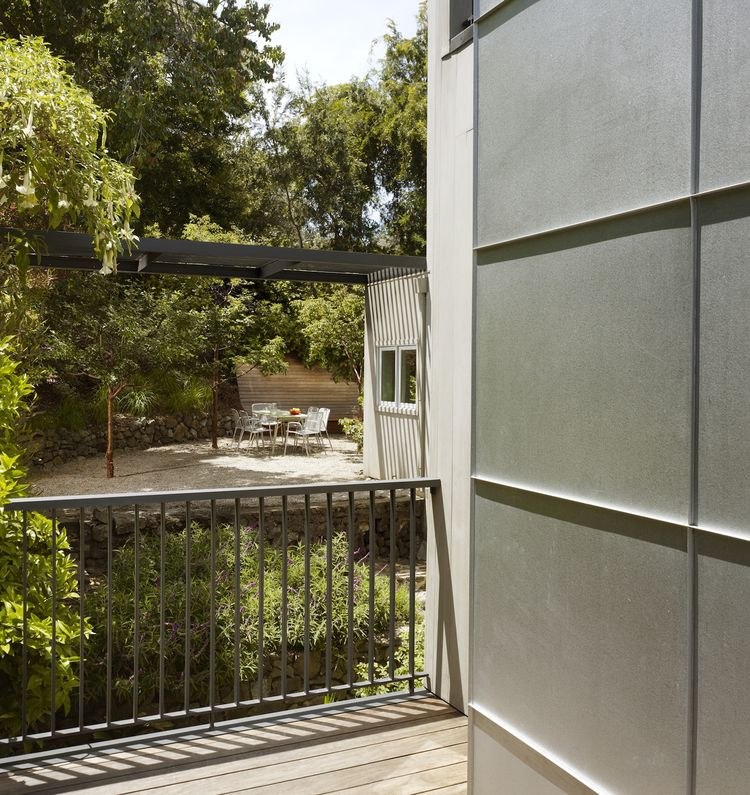 "Galvanized sheetmetal chimney cladding, a steel trellis and steel railings bring modern details and materials to the exterior. The steel trellis acts as a ""drag strut and anchor"" for the whole house, providing necessary seismic reinforcement while minimiz"