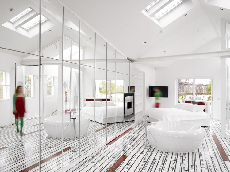 """""""We edited down until the house just became a pure white box,"""" Rogers says. """"By the end of it all, we rethought everything except the internal walls."""" The bright, skylit master bedroom is accented with <a href="""" http://www.richardwoodsstudio.com/"""">Richard"""