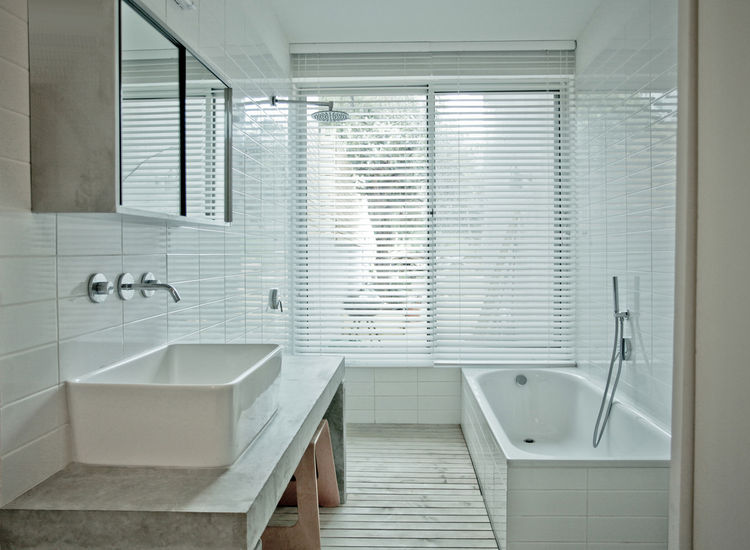 The master bath is a clean and spare space, a mixture of white and concrete.
