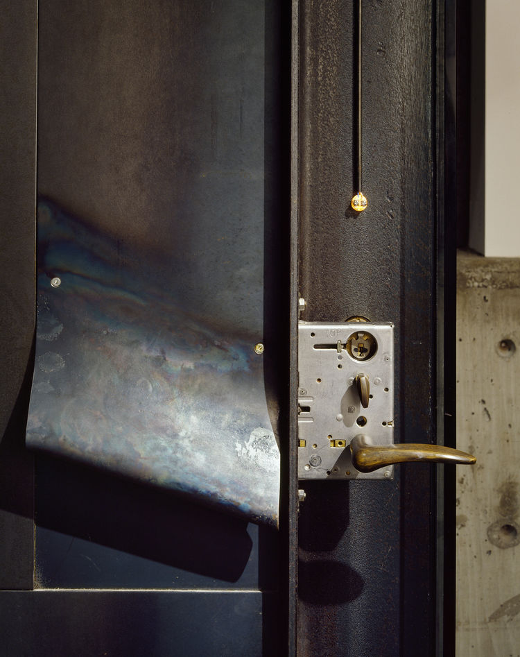"""Of the entry door lock on his 'Hot Rod House,' architect Tom Kundig says: """"I was working on the door and thinking, 'That's cool, the way it works—why not put it on backward so you can see it move?'"""" Photo by Benjamin Benschneider."""