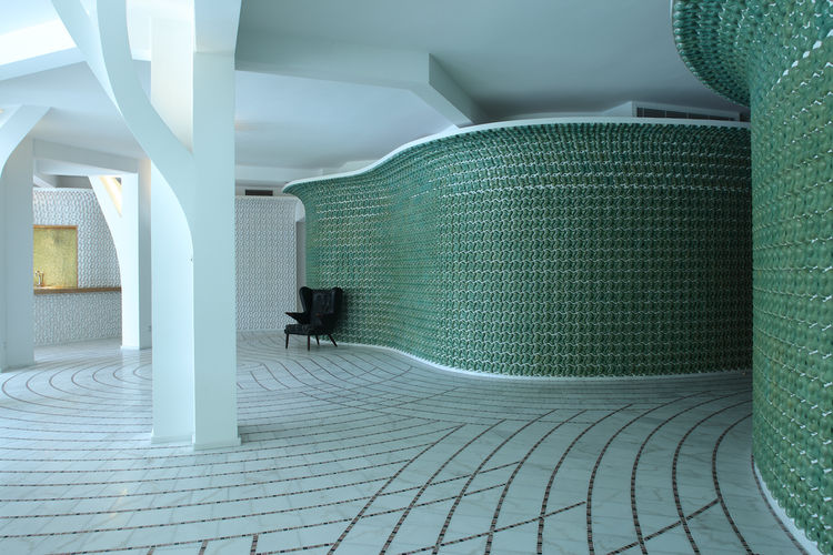 In their Villa for an Industrialist in Shenzhen, China, architects Peter Lynch and Ahlaiya Yung opted for curving walls finished in green and white high-relief slip-cast ceramic tiles. Photo by Chen Yan (VA-PHOTO).