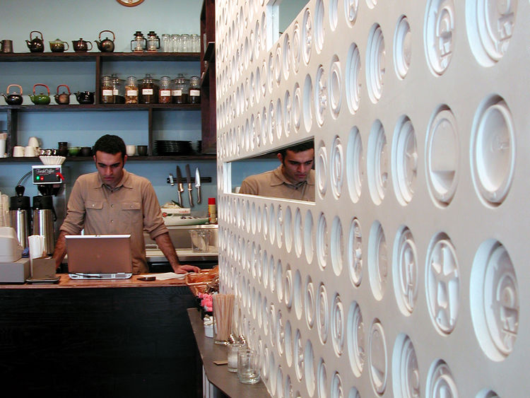 At the Ini Ani Coffee Shop in New York, Lewis.Tsurumaki.Lewis, a 'lid wall'—lined with 479 plaster casts of takeout coffee lids—leads to the front counter. The project was built in three months for $40,000. Photo courtesy of Lewis.Tsurumaki.Lewis.