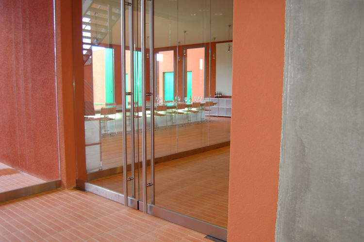 A pair of glass doors open to the tasting room, also designed by Renzo Piano.