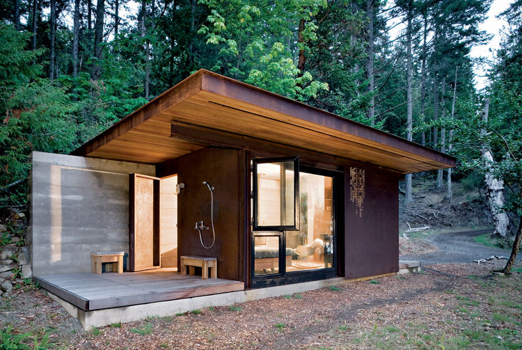 """This 191-square-foot cabin near Vancouver and its glass facades """"forces you to engage with the bigger landscape,"""" architect Tom Kundig says, but it seals up tight when its owner is away. The unfinished steel cladding slides over the windows, turning it in"""