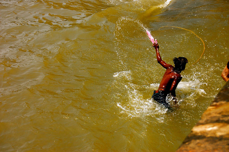 During the festival of Holi, Mumbai's inhabitants take to the streets and paint each other. This kid had enough and jumped in the harbor to wash himself clean.