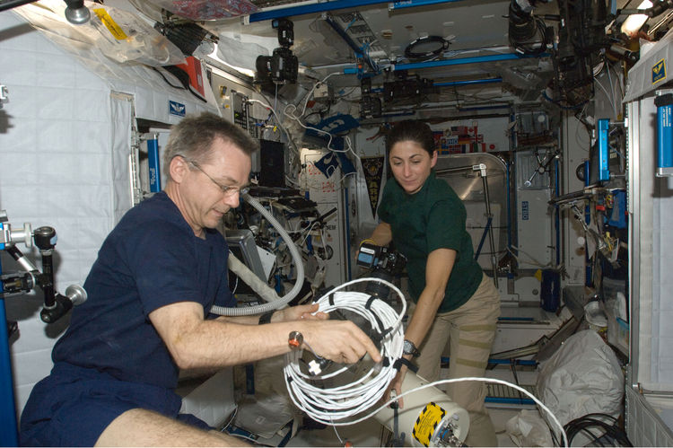 Canadian Space Agency astronaut Robert Thirsk and NASA astronaut Nicole Stott, both Expedition 21 flight engineers, work in the Harmony node of the International Space Station. Photo taken October 11, 2009. <br /><br />Courtesy of NASA