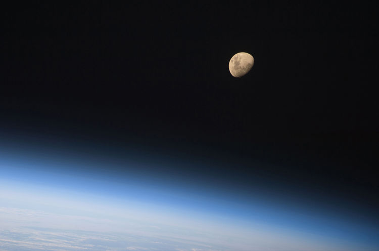 A gibbous moon is visible above Earth's atmosphere, photographed by an STS-128 crew member on the Space Shuttle Discovery during flight day three activities. Photo taken August 30, 2009. <br /><br />Courtesy of NASA