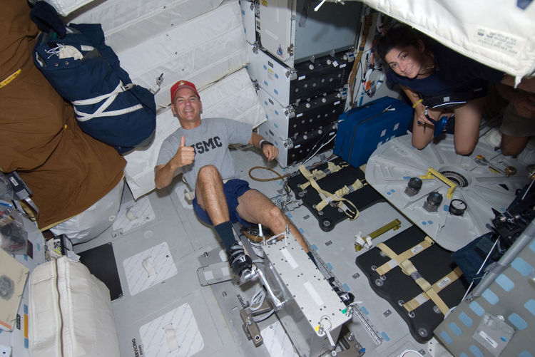 "Astronaut Rick Sturckow, STS-128 commander, gives a ""thumbs-up"" signal while exercising on a bicycle ergometer on the middeck of the Earth-orbiting Space Shuttle Discovery. Astronaut Nicole Stott, mission specialist, is visible at right. Photo taken Augus"