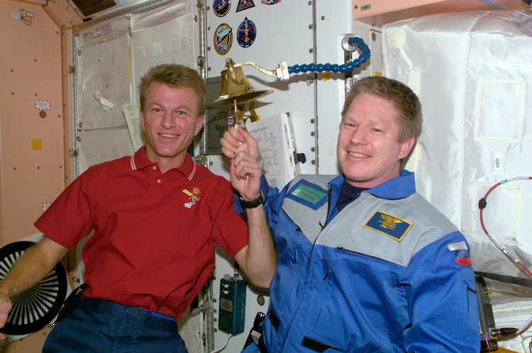 Astronauts Brent W. Jett, Jr. (left) and William M. Shepherd participate in an old Navy tradition of ringing a bell to announce the arrival or departure of someone to a ship. The bell is mounted on the wall in the Unity node of the ISS. The bell-ringing t