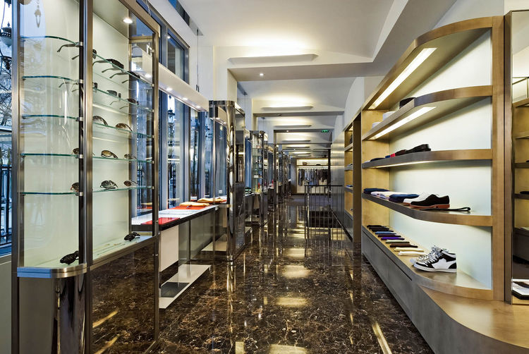 The men's accessory gallery houses shoes and glasses on its sycamore, nickel and acid-etched glass shelves. Photograph by Jean Philippe Caulliez.
