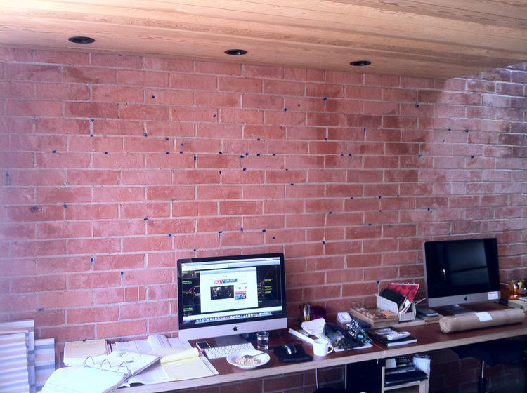 In planning to install the brackets along the brick wall, we spaced the brackets so that we would have all the holes fall on mortar joints, where the majority of the existing patches already were (as seen in this photo, we mapped all the holes in the wall
