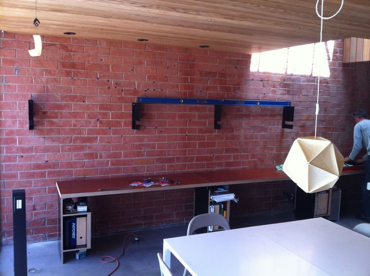 Because we planned to have a single wood plank as our shelf, each bracket had to be mounted perfectly level and aligned with one another, and spaced so that the holes fell on the mortar joint of the brick.