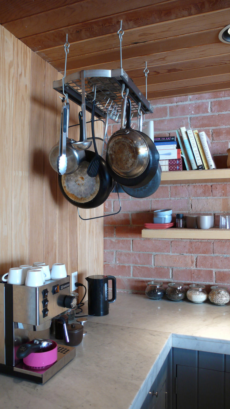 Our pot rack, espresso machine, cookbooks and jarred ingredients make the kitchen part lab, part library.