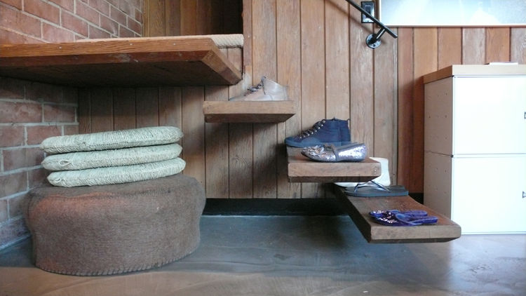 One of the great details in the Courtyard Apartments is the cantilevered stair. Our steps double as shoe storage as we have a no-shoes policy upstairs. Under the stairs we can store flexible seating, such as this felt pouf from OK and grass tatami cushion