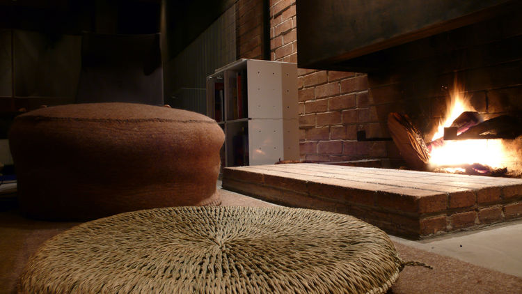 The round felt pouf and tatami cushions enable close fireside gathering.