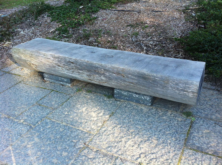 A large tree trunk bench—shown here raised off the ground with two stone slabs from the Presidio in San Francisco—would be perfect on a concrete slab.