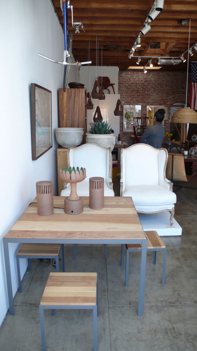 Grain, a small furniture store in Atwater Village, makes a nice outdoor table: powder-coated steel legs and frame with carefully selected 2x6 boards for the tops. It's nice and simple and matches the aesthetic of the Craig Ellwood apartment building, and