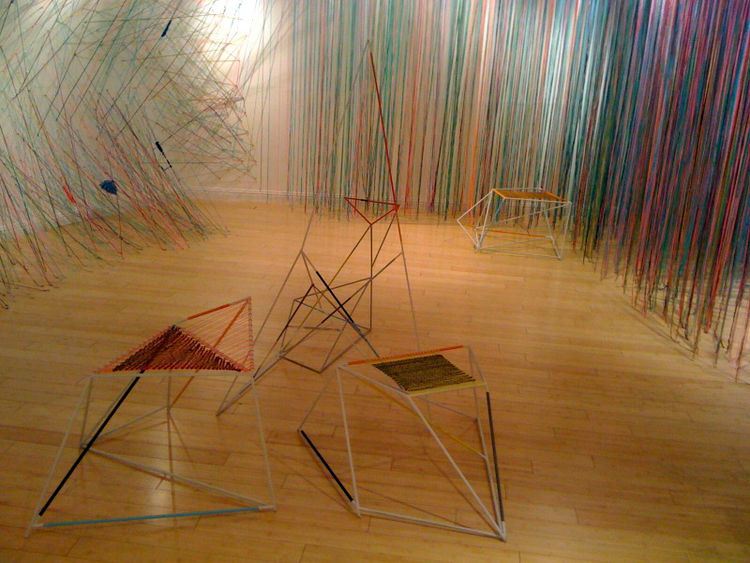 In the center of the installation, handmade chair sculptures mirror the colorful geometric world of string. The pieces are composed of crisscrossing steel rods painted white with brightly colored rope and yarn braided and knotted throughout to complete th