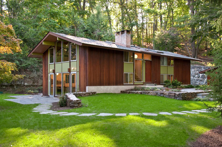 "The structure's exterior, however, finished in redwood siding—chosen for its sturdiness and resistance to rot—""had held up very well—we just gently power-washed it,"" Depardon says. The architects chose a moss green for the infill panels, as the originals"