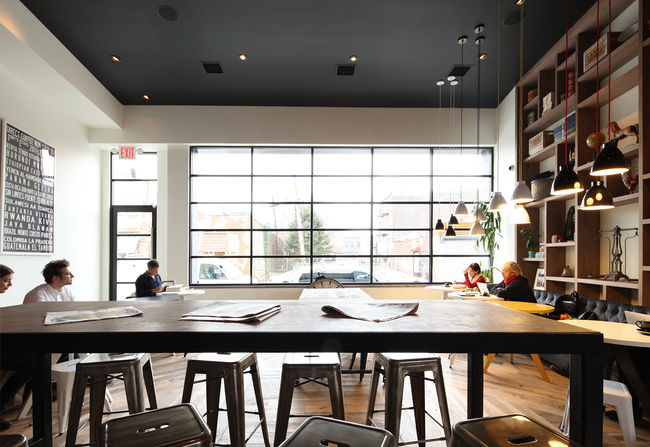 """The brightly lit cafe boasts ample tables and seating for patrons to read, converse, or catch up on work. """"The main objective was to create an environment where people in the community would come, hang out and stay for a while,"""" says Nema."""