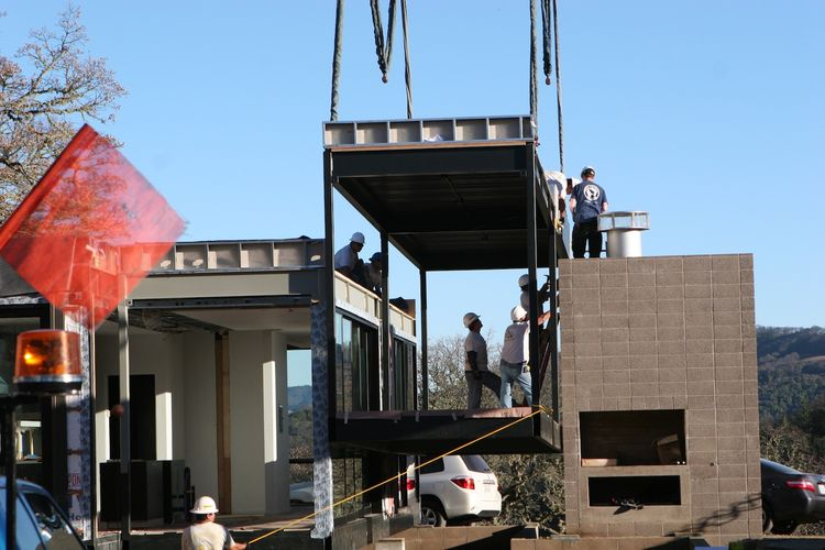 Here's one of the outdoor covered deck modules being lowered into place adjacent to the fireplace.