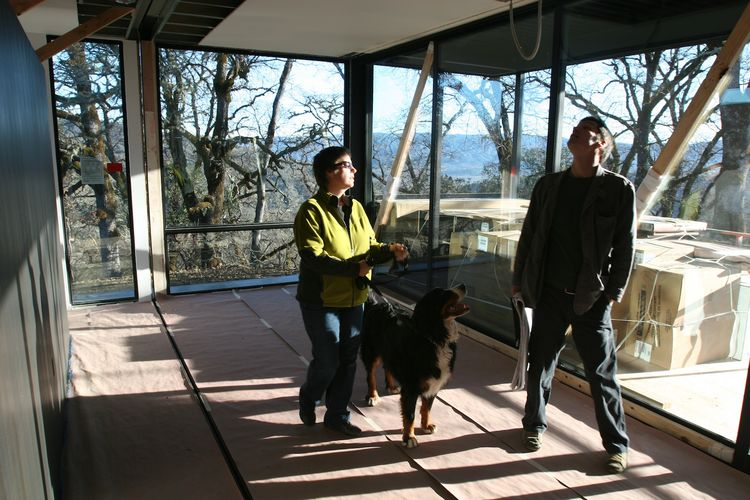 "Abbie, Stella (the Burton's other dog), and Riley, the project architect for Marmol Radziner, stand in the master bedroom, just after the last module was set. ""You can see the open drywall seam in the ceiling that will be closed up over the next six weeks"