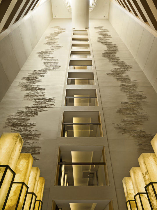 An installation of crimped stainless steel sheets drift up the limestone walls of the elevator banks, a ten-story installation by the Japanese artist Hiroshiwata Sawada that mimics the light patterns and ripples of the water in the reflecting pools below.