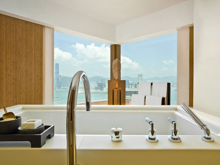 Sliding pocket doors disappear into the bathroom wall, revealing a soaring view of the harbor from the capacious soaking tub. A wood-grain sandstone sculpture by Taiwanese sculptor Marvin Minto Fang anchors the space and draws the eye forward and out.
