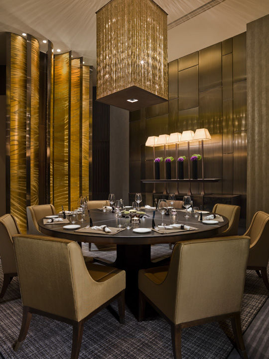 A private dining room in the restaurant is all golden hues, with brushed bronze walls and silk-upholstered chairs set atop a tweedy rug. The chandelier is assembled from bronze rods that resemble bamboo stalks. On the left, a screen made of banana-shaped