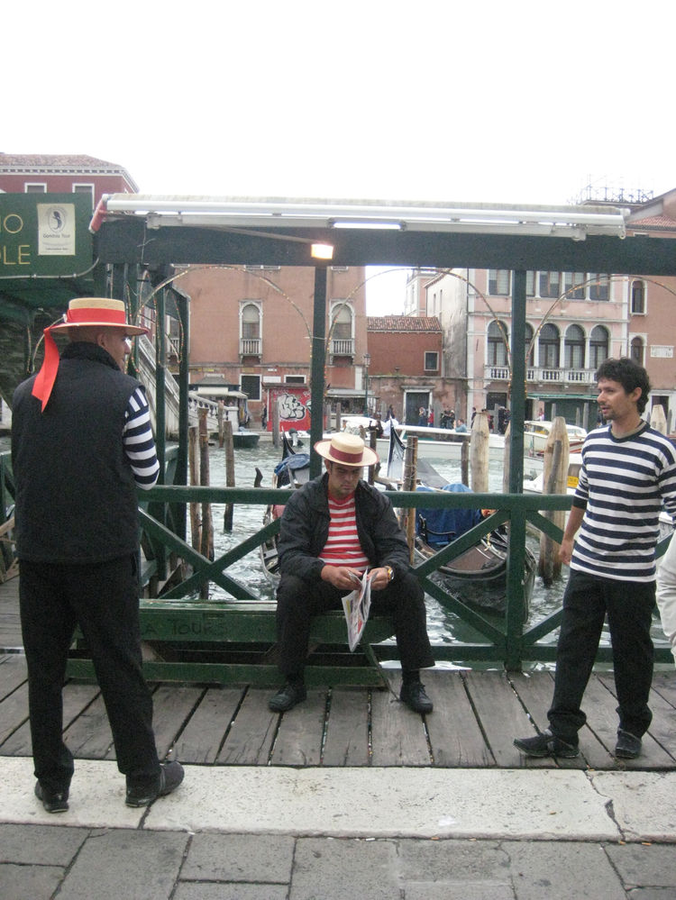 Gondoliers taking a quick minute to relax, catch up, and read the paper.