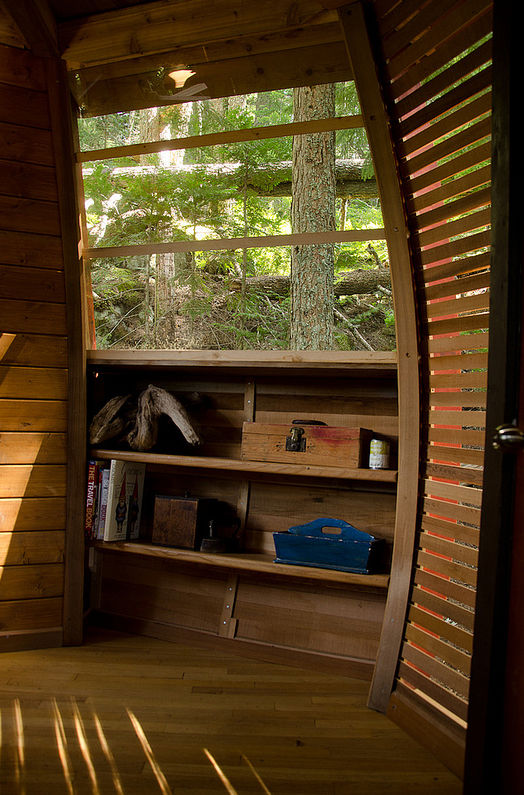 """Inside, the tree house boasts built-in furniture Allen crafted from his free Craigslist finds. """"If I would have used pre-built furniture, it would have just dominated the space,"""" says Allen."""