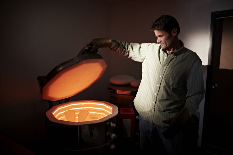 Wisner can judge the temperature inside his kiln by the color of the clay as it's firing.