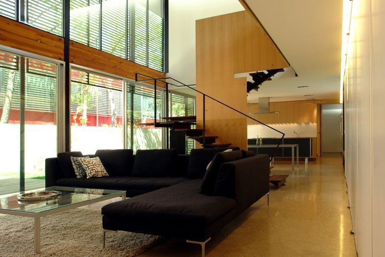 The front entrance opens onto the expansive double-height sitting room with a large sectional couch. The white wall on the east side of the house is entirely dedicated to built-in storage, with recessed lighting along the upper edge.
