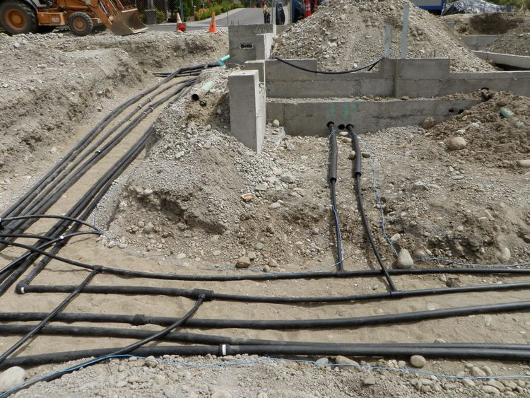 The ground source wells are tied together via a set of manifolds fused together a few feet below the ground surface. Between additional solar electrical conduit, the ground source piping, rainwater piping, and normal utilities (stormwater, water, electric