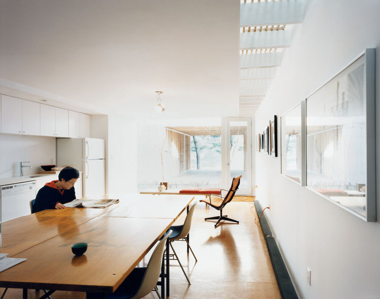 Kim reads the newspaper in the all-white kitchen. White paint, which requires fewer coats than color, was a money-saving strategy. The desk chairs and aluminum lounge chair are both Eames, courtesy of Fernandez's scavenging.
