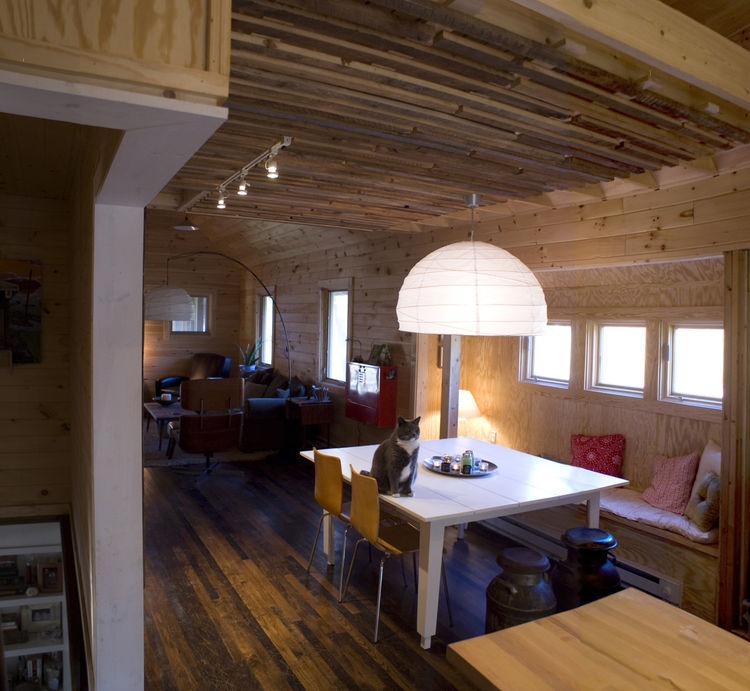 In the dining room, the ceiling was dropped over the dining room to provide more intimate setting. Strips of salvaged hemlock and chestnut wrap the interior wall and ceiling. A loft for naps and overnight guests is above.