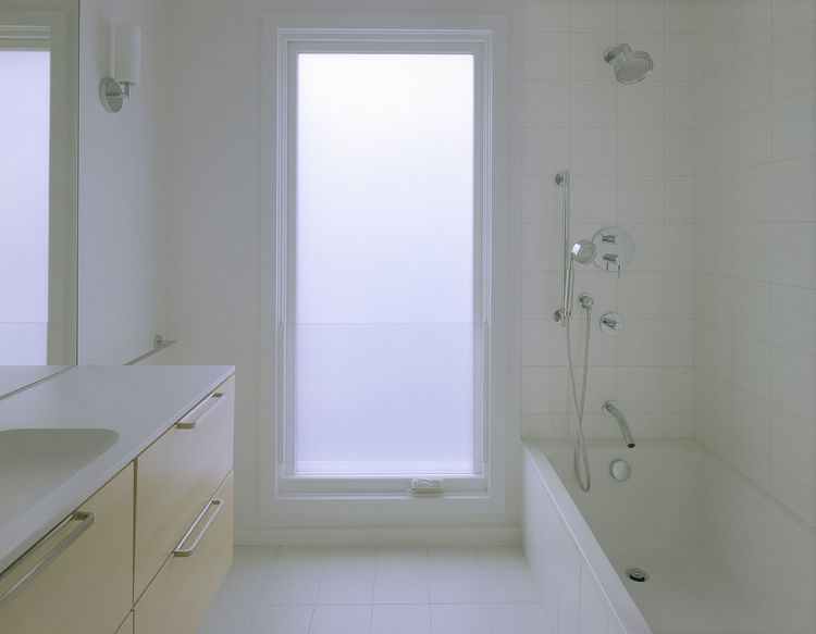 An IKEA vanity is suspended off the floor, making it easy to clean. The Spartan style and sense of space is enhanced here, as elsewhere in the home, by the oversized windows, white hues, and lack of architectural frippery or frills. Kohler shower fixtures