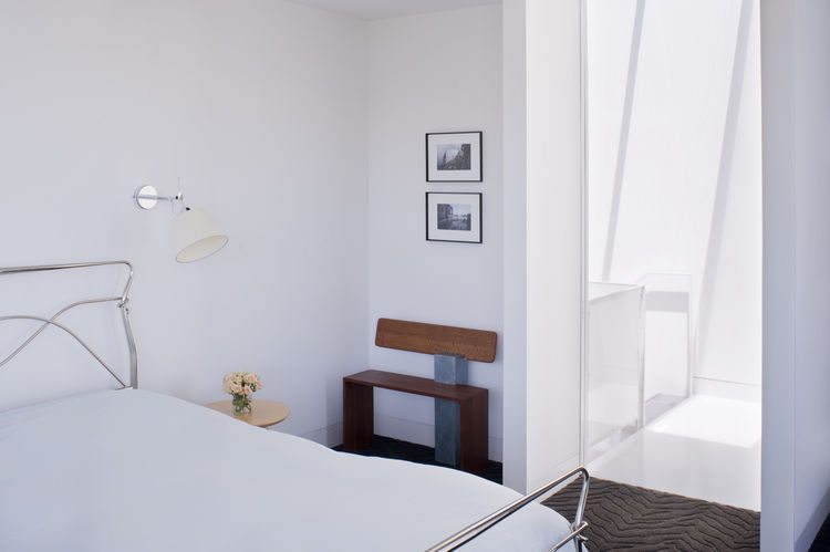 "Back in the master bedroom, the designers installed Tolomeo wall sconces by <a href=""http://www.artemide.us/"">Artemide</a> next to the bed and placed a bench next to the door made by Hart's uncle, Peter Czuk of <a href=""http://www.czukstudio.com/"">Czuk St"