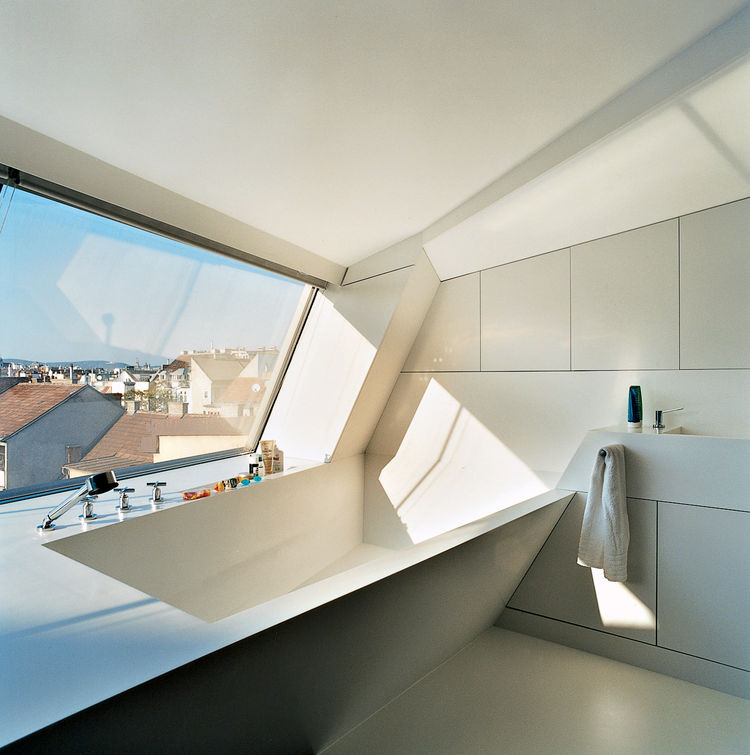 The cavity for the bathtub is part of the same continuous form-world as House Ray 1's sloping roof­scape. The white tub is made from Corian; the faucet is by Dornbracht.