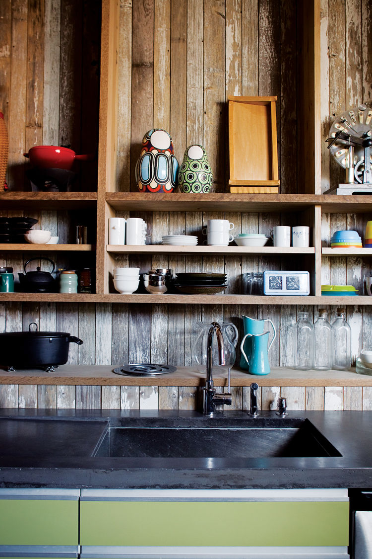 With its reclaimed-wood cladding, the kitchen is a rough-and-ready backdrop for the family's tableware.