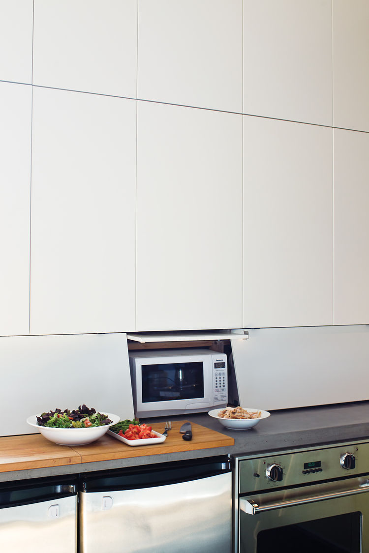 """<p><h2>Behind Closed Drawers</h2></p> To continue the spare lines of the kitchen cabinets, John designed and built an """"appliance garage"""" by cutting up Ikea drawer fronts to build hinged doors that enclose an area beneath the cabinets, hiding a toaster, mi"""
