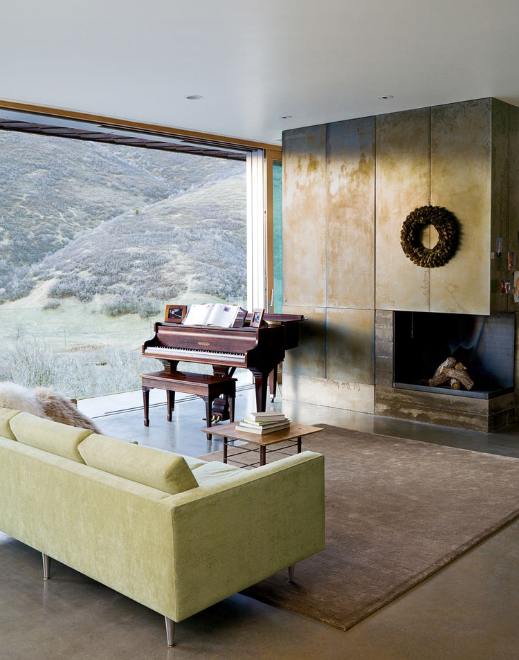 """In the living room, the canyon vistas share center stage with the wood-burning fireplace (attractive despite going through an """"awkward phase"""") and a rare quarter-grand piano from the late 1800s, a Mooney family heirloom. The polished concrete floors are r"""