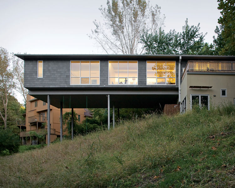 The Arnolds' bedroom and living area float over the hillside, the large windows allowing light to flood in from both sides. A bamboo-enclosed deck sits atop the house's foundation.