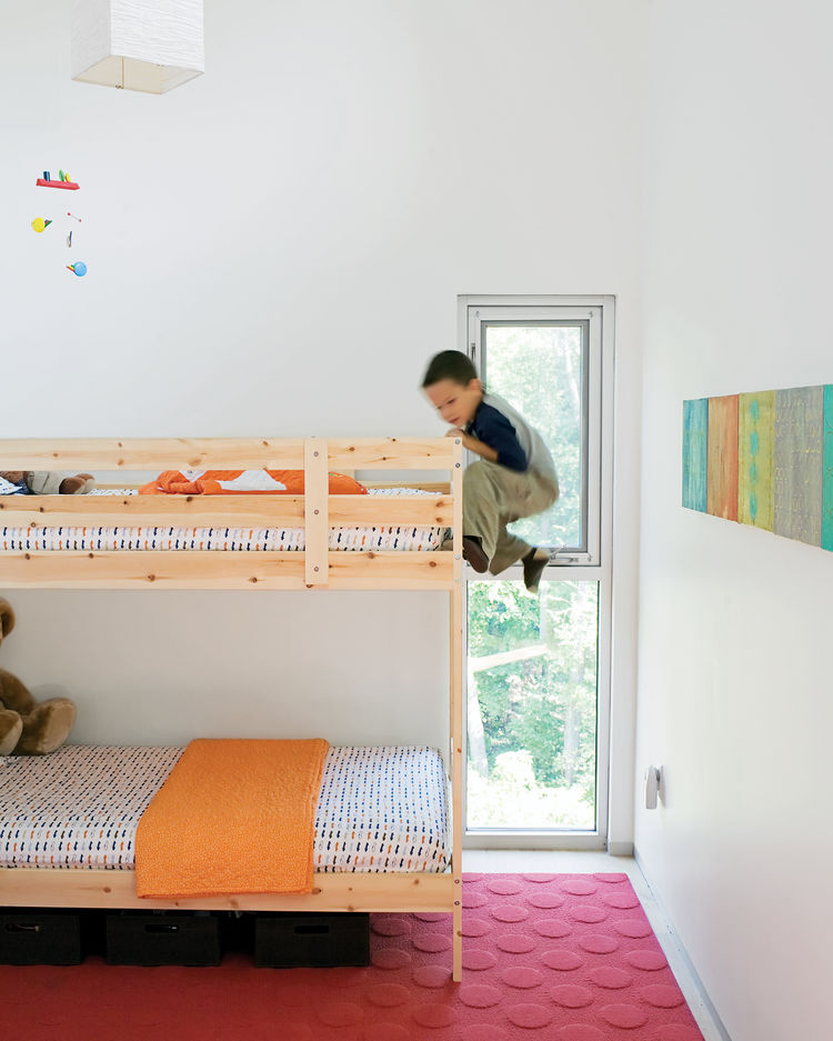 In the kids' room, Jack climbs the bunk bed he shares with his little brother, James. The paintings on the wall were done by their mom.