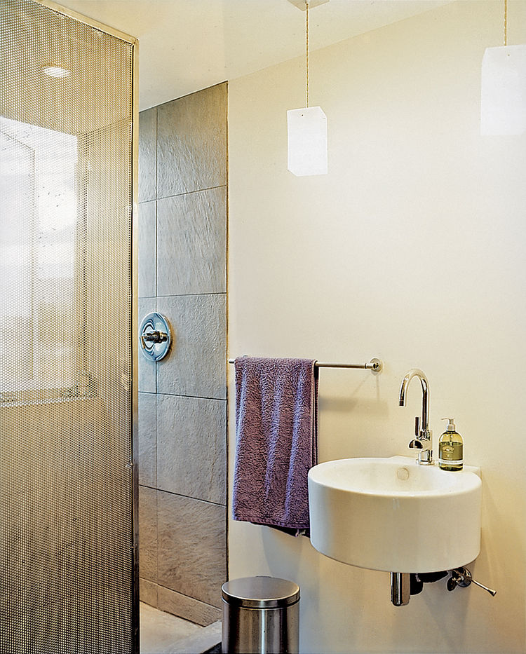 A perforated metal screen serves as a shower curtain.
