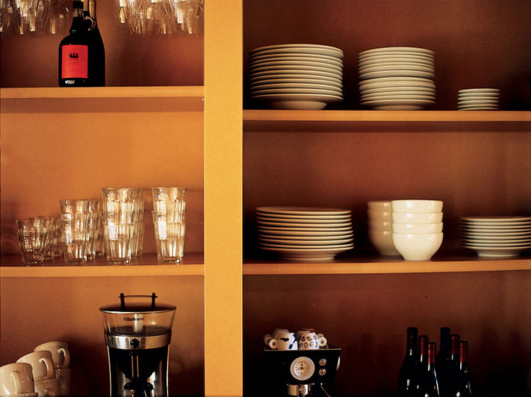 "The kitchen cabinets where the Scommegnas store their dishes are open, creating what Vetter calls a ""nonfussy, more direct approach to the storage of your daily items."" Scommegna allows that a pair of doors easily could have been added without much troubl"